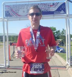"Posing with medal, mug for completing the ""Uncle Sam Slam"" (5K + 10K), and age group award glass. Ah, sweet swag - isn't that the American Dream?"