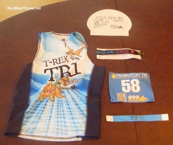 "Triathlon gear. Clockwise from top right: swim cap in wave color, ankle strap with timing chip, bib for the run, bike tag with race number, ""tri top"" with the event's logo."