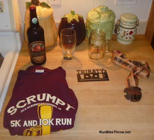 Check out the swag! Clockwise from bottle: age group winner glass, finisher's mason jar mug, medal / bottle opener, metal hanger for the Thirsty 3 medals, shirt. (Okay, I bought the bottle.)