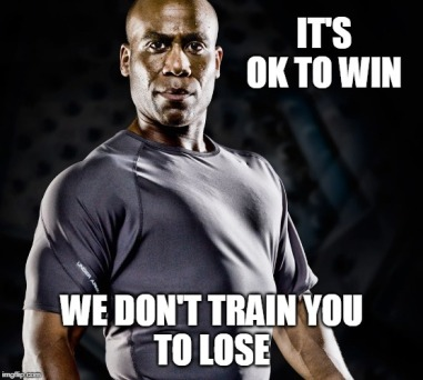 Meme: Trainer with arms folded saying IT'S OK TO WIN - WE DON'T TRAIN YOU TO LOSE